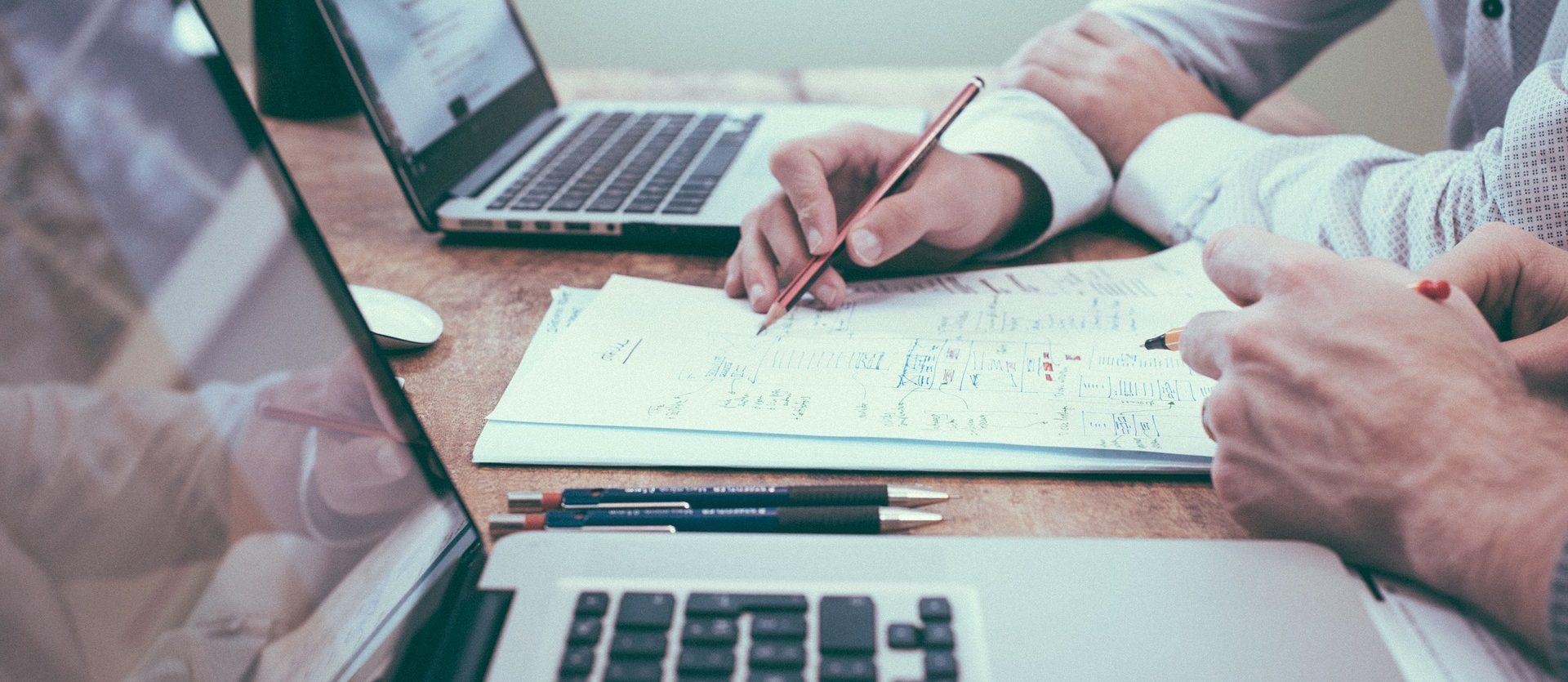 Dois profissionais homens à frente de dois notebooks e entre eles uma folha com dados técnicos com os quais os profissionais estão discutindo