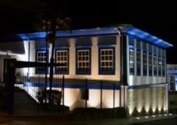 casa branca e azul, com arquitetura antiga iluminada à noite por luzes do chão
